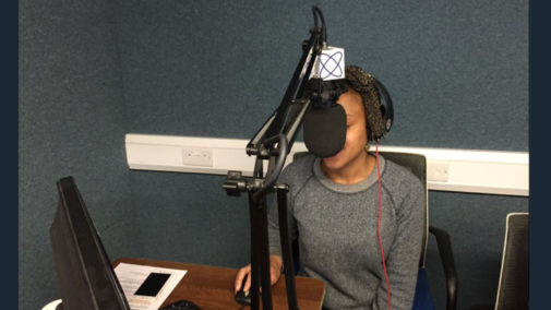 A young black woman in a radio studio with a big microphone in front of her face.
