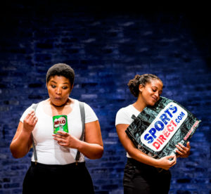 Two women of colour in white t-shirts and black trousers. One stares amazed into a Milo tin. The other lovingly holds a Sports Direct Bag