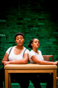 Two women of colour sit at a table with their arms resting on the top. They are wearing matching white t-shirts and they are looking straight forwards with a strong expression on their faces, like they mean business.