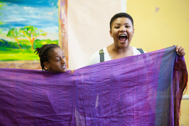 two black women posing with a purple scarf during rehearsals